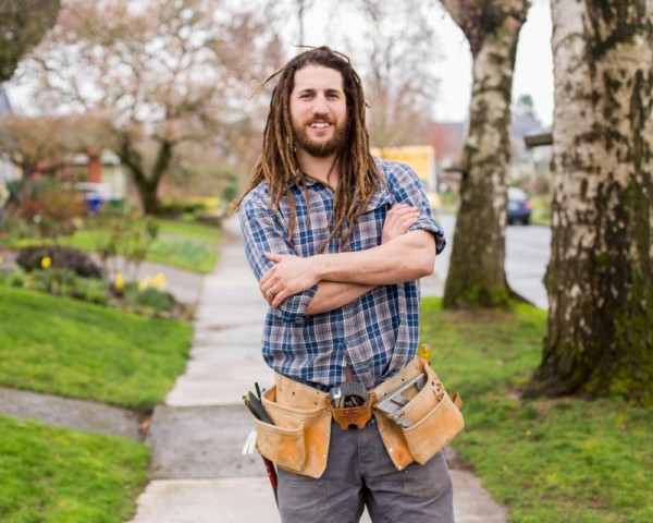 Man with tool belt standing on sidewalk with arms crossed and smiling