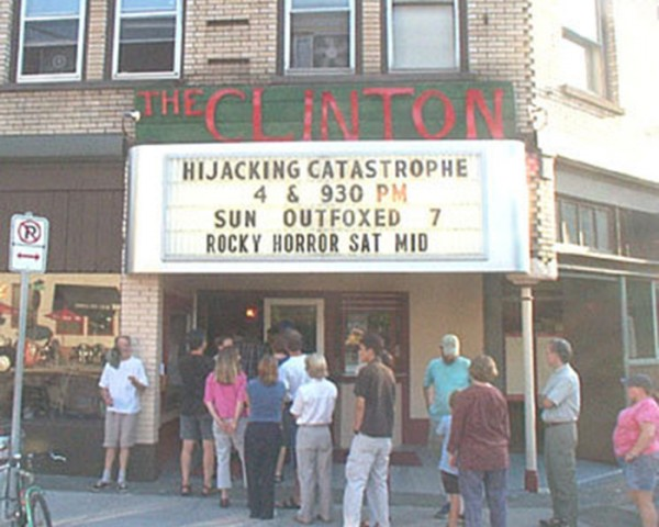 people lining up outside movie theater under marquee sign