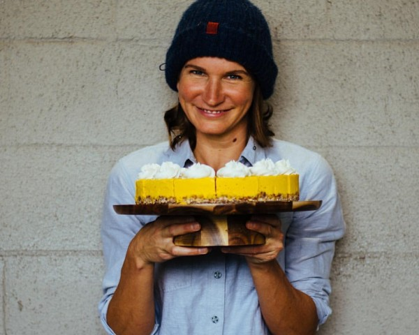 smiling woman holding a cake on a platter