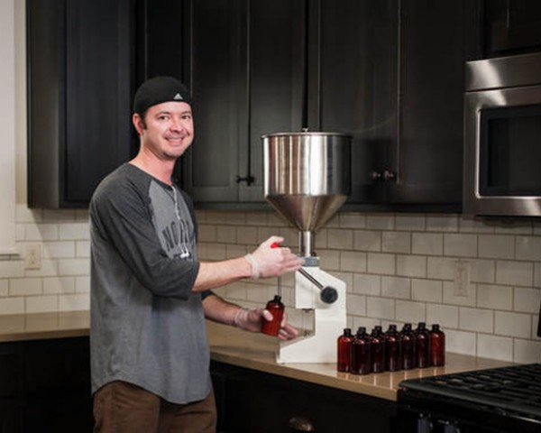 Man filling bottles with machine in kitchen